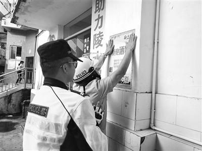 路管员在车站张贴宣传海报      记者许光伟 摄